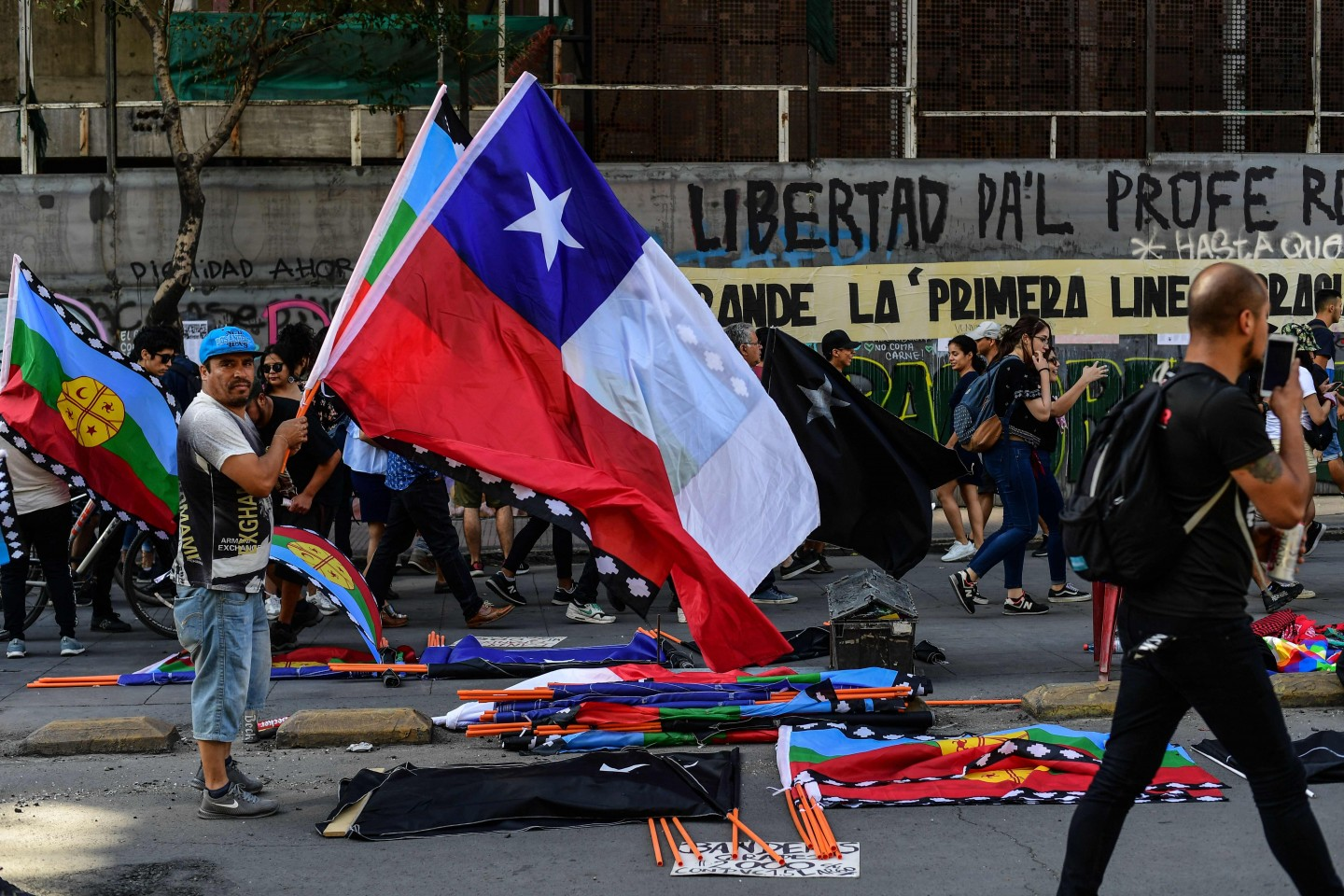 Artists sell merchandise making reference to the social crisis going on in Chile, near Plaza Italia square, site of protests and clashes in Santiago, on November 22, 2019. Since October 18, furious Chileans have been protesting social and economic inequality, and against an entrenched political elite that comes from a small number of the wealthiest families in the country, among other issues. (Photo by Martin Bernetti/AFP)
