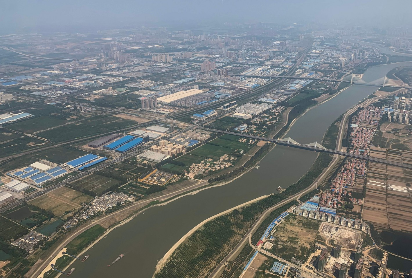 "Wuhan, a city gloriously named the ""thoroughfare to nine provinces"", is the epicentre of the deadly new coronavirus. This aerial view taken on 6 September 2019 shows the Yangtze River in the city of Wuhan in Hubei Province. (Hector Retamal/AFP)"