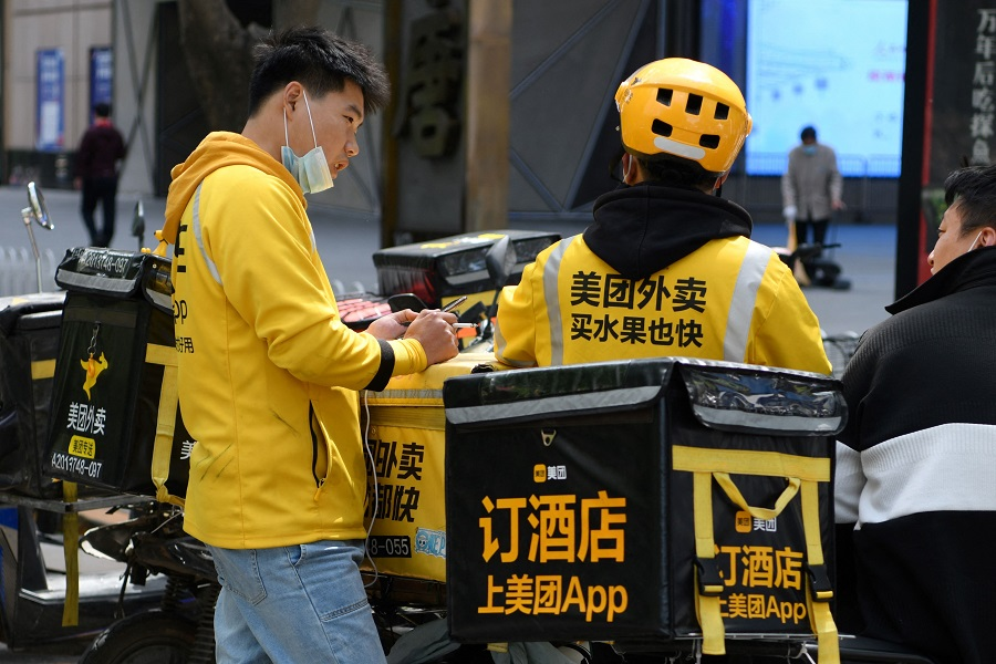 Delivery riders for Meituan, one of China's biggest food delivery firms, chat while waiting for orders outside a restaurant in Beijing, China, on 27 April 2021. (Greg Baker/AFP)
