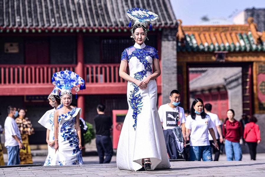 Models display cheongsams, also known as qipaos, during the Shenyang Cheongsam Culture Festival at Shenyang Imperial Palace in Shenyang, Liaoning, China, 23 September 2020. (STR/AFP)