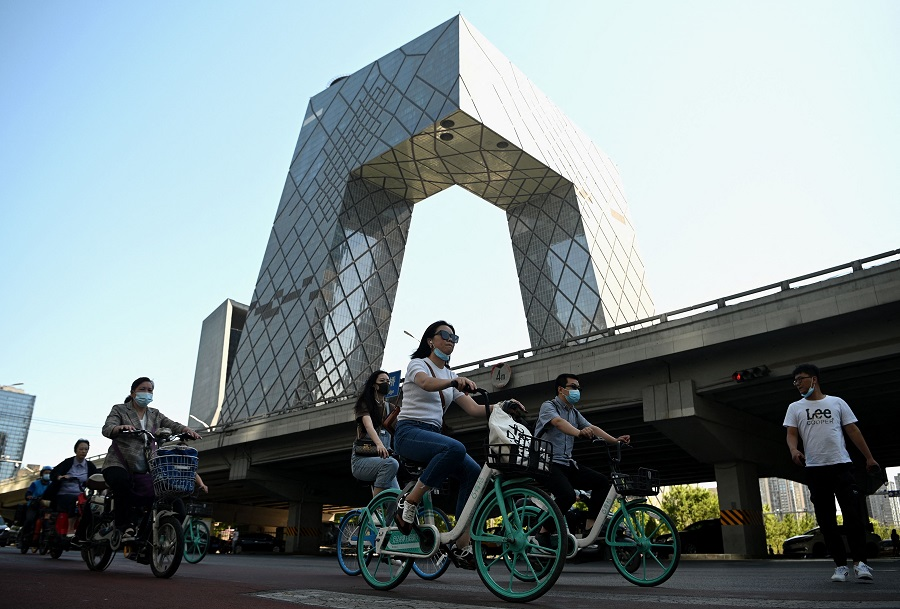 This photo taken on 3 June 2021 shows people cycling along a street during the rush hour in Beijing, China. (Noel Celis/AFP)