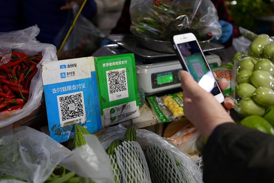 A customer makes a payment using a Wechat QR payment code (centre) via her smartphone, next to an Alipay QR code (left), at a vegetable market in Beijing on 3 November 2020. (Greg Baker/AFP)