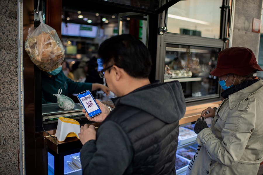 This picture taken on 28 October 2020 shows a customer (left) making an electronic payment with Alipay on his smartphone for his food at a restaurant in Beijing. (Nicolas Asfouri/AFP)