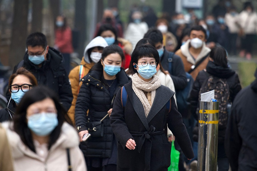 People walk along a street in Beijing, China, on 5 March 2021. (Noel Celis/AFP)