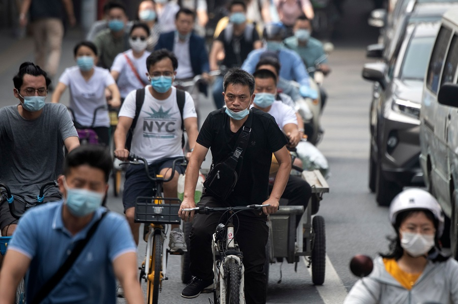 People commute on a street during the morning rush hour in Beijing on 20 July 2020. (Noel Celis/AFP)