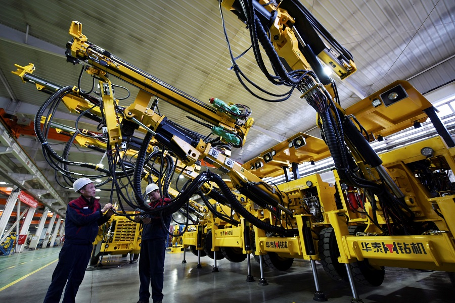 This photo taken on 19 December 2020 shows employees working on a drilling machine assembly line at a factory in Zhangjiakou, Hebei province, China. (STR/AFP)