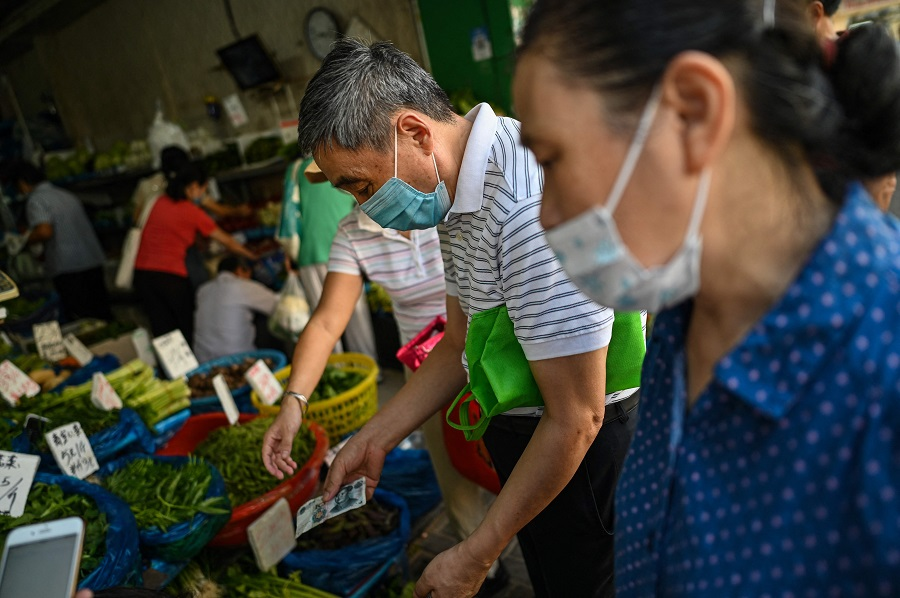 People buy vegetables at a shop in Shanghai, China, on 28 September 2021. (Hector Retamal/AFP)