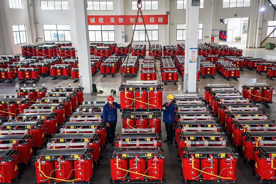 This photo taken on 4 January 2021 shows employees working on a dry-type transformer production line at an electrical production factory in Hai'an, Jiangsu province. China. (STR/AFP)
