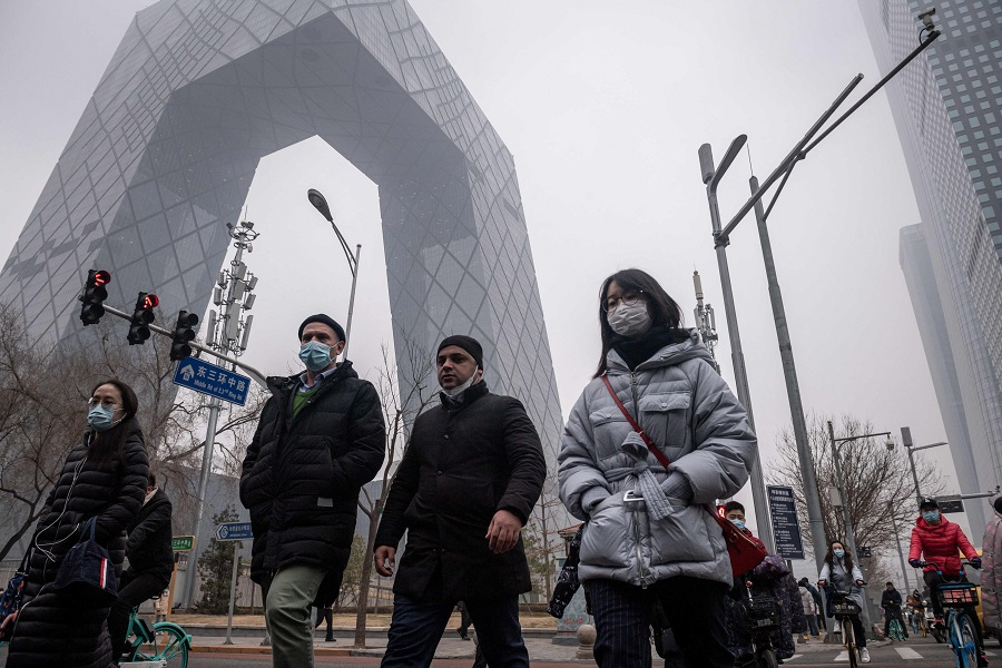 People commute during the morning rush hour in the financial district in Beijing, China, on 4 March 2021. (Nicolas Asfouri/AFP)