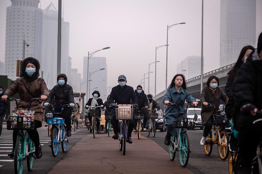 People commute during the morning rush hour in the financial district, Beijing, China, on 4 March 2021. (Nicolas Asfouri/AFP)