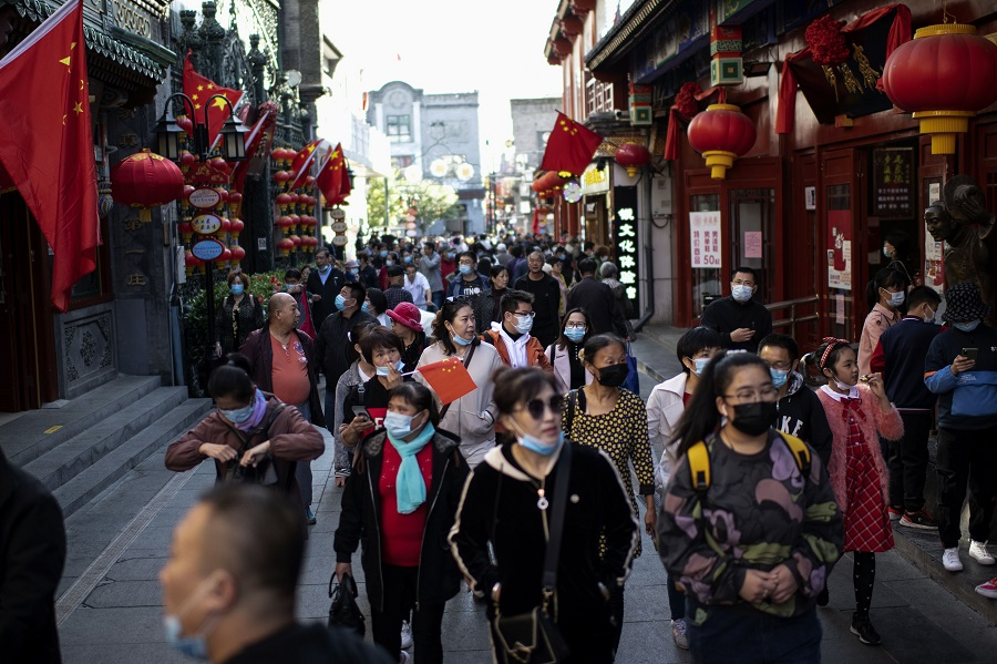 "People wearing face masks walk along Qianmen street to shop during the country's national ""Golden Week"" holiday in Beijing on 5 October 2020. (Noel Celis/AFP)"