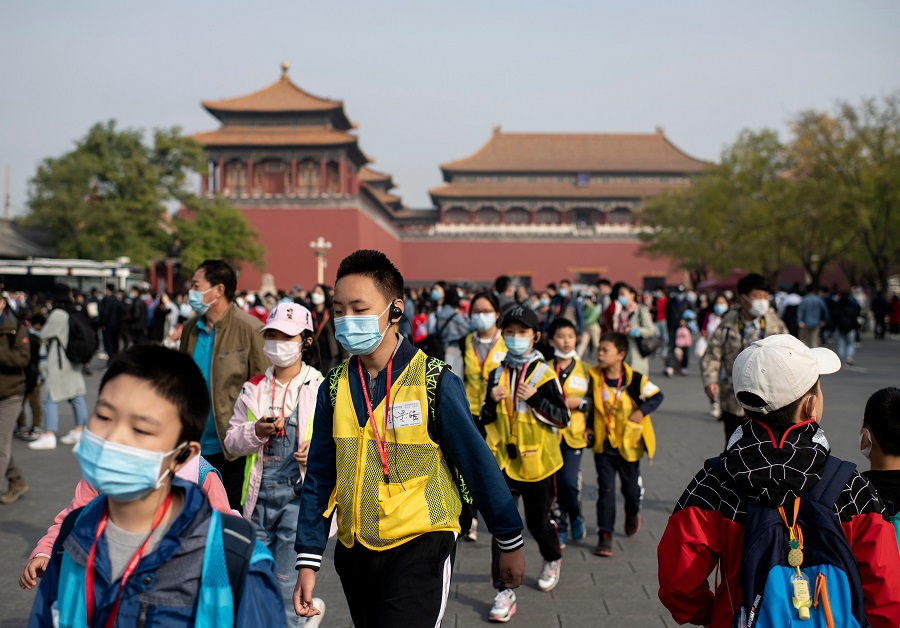 "People wearing face masks walk outside the Forbidden City during the country's national ""Golden Week"" holiday in Beijing, China, on 8 October 2020. (Noel Celis/AFP)"