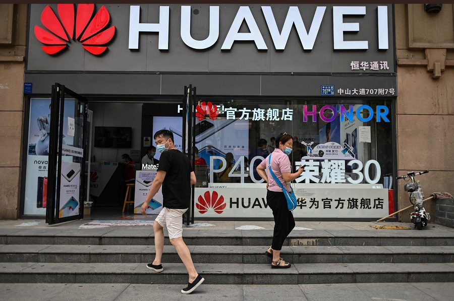 People wearing face masks walk outside a Huawei store in Wuhan, Hubei, China, on 26 May 2020. (Hector Retamal/AFP)