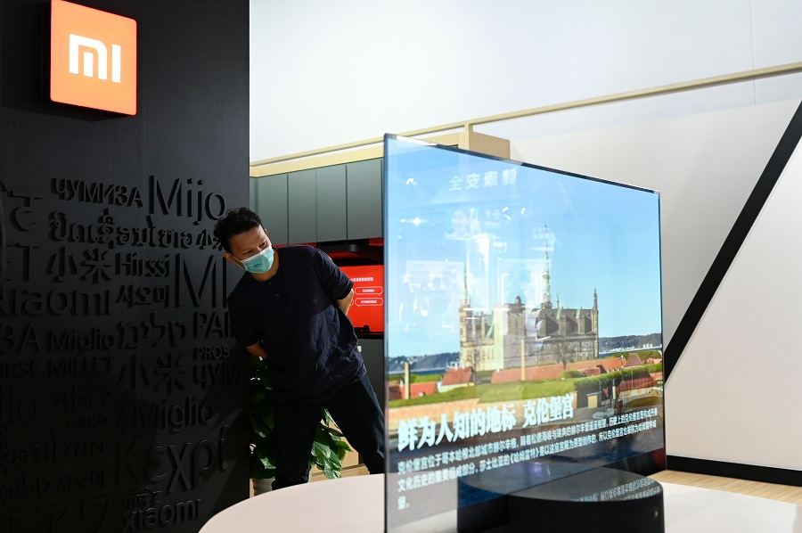 A man looks at a Xiaomi TV at the Chinese technology company Xiaomi booth at the China National Convention Centre, the venue for the upcoming the China International Fair for Trade in Services (CIFTIS) in Beijing on 3 September 2020. (Wang Zhao/AFP)