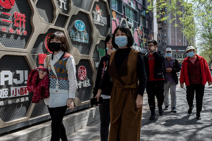 People walk along a street during lunch time in Beijing, China, on 14 April 2021. (Nicolas Asfouri/AFP)
