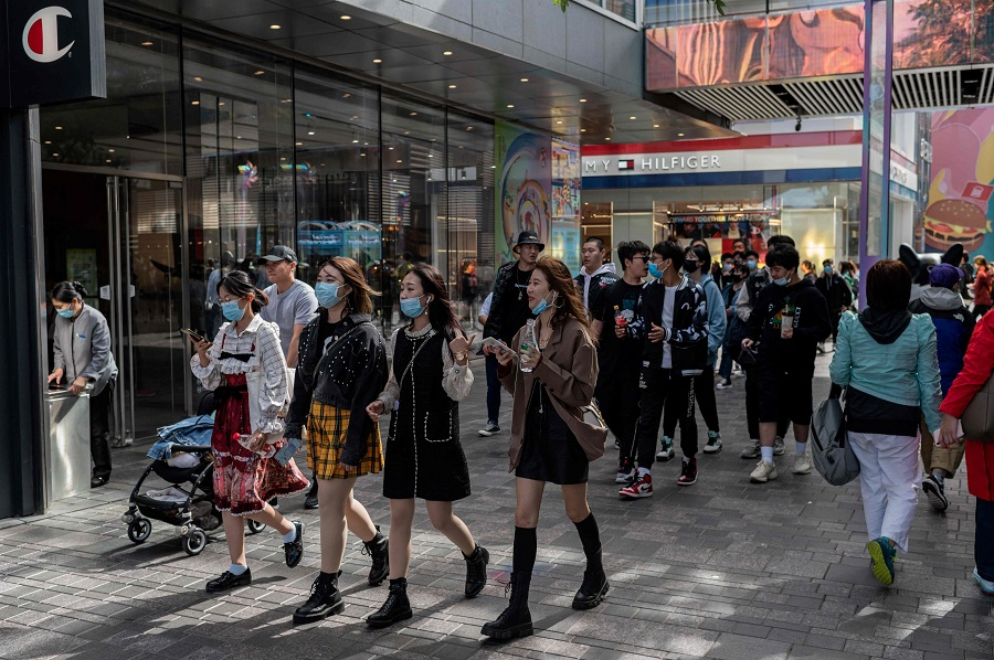 "People wearing face masks walk outside a shopping mall during the country's national ""Golden Week"" holiday in Beijing on 2 October 2020. (Nicolas Asfouri/AFP)"