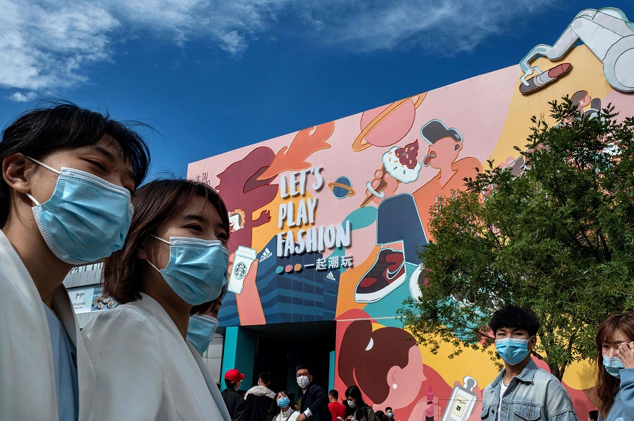 "People wearing face masks as a preventive measure against the Covid-19 coronavirus walk outside a shopping mall complex during the country's national ""Golden Week"" holiday in Beijing on 2 October 2020. (Nicolas Asfouri/AFP)"