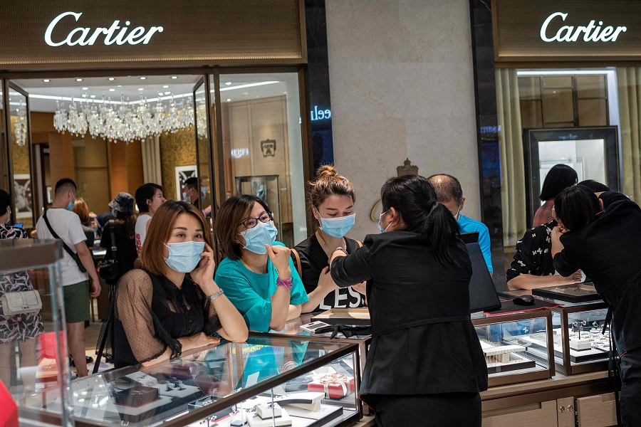 People look at jewellery in a mall in Beijing on 14 August 2020. (Nicolas Asfouri/AFP)