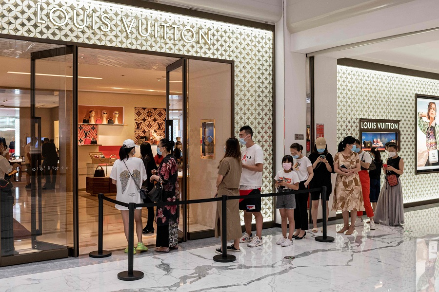 People queue to enter a Louis Vuitton shop at a mall in Beijing on 14 August 2020. (Nicolas Asfouri/AFP)