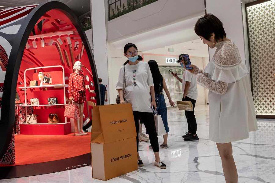 A woman poses for a photo with her Louis Vuitton shopping bags in a mall in Beijing on 14 August 2020. (Nicolas Asfouri/AFP)