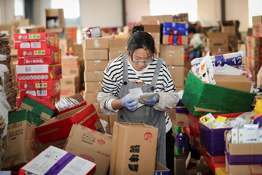 An employee checks the delivery information for packages ahead of the upcoming Singles' Day Festival at an e-commerce warehouse in Lianyungang, Jiangsu, China, 2 November 2020. (STR/AFP)
