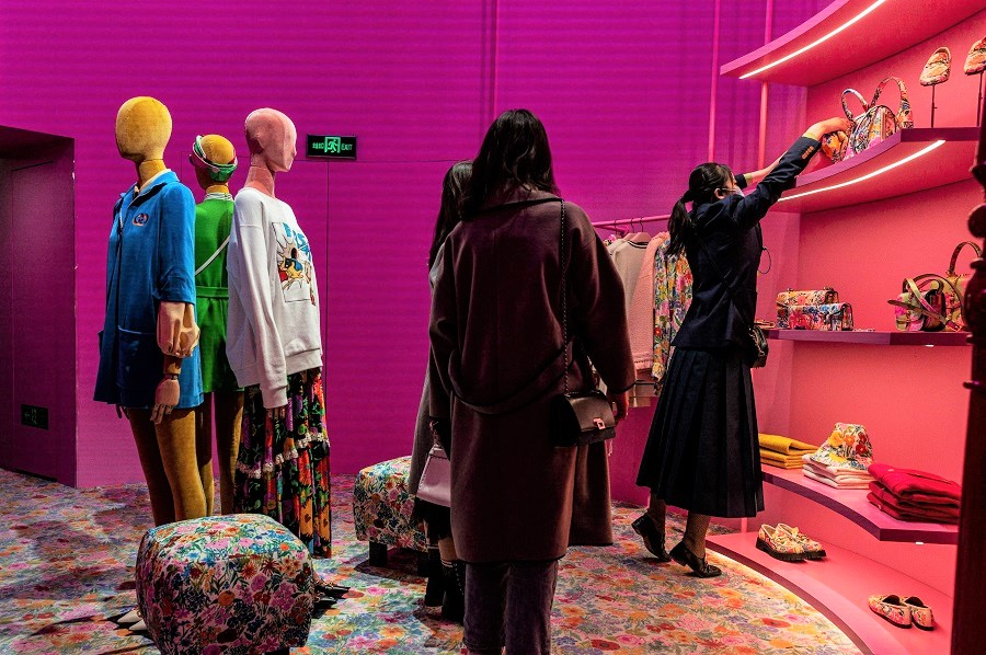 People shop inside a Gucci shop as an employee (right) grabs an item in Beijing, China, on 13 April 2021. (Nicolas Asfouri/AFP)