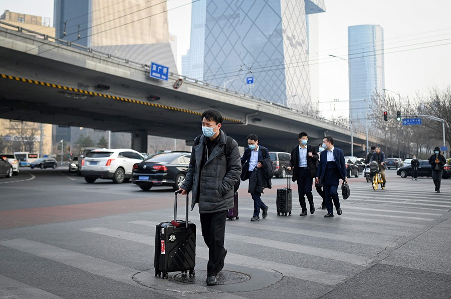 Pedestrians cross a street with their luggage in the central business district of Beijing, China on 8 March 2021. (Wang Zhao/AFP)