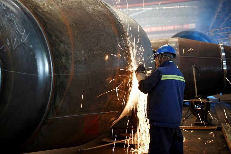 An employee welds truck parts at a mixer truck manufacturing factory in Zhangjiakou, Hebei province, China, on 8 December 2020. (STR/AFP)