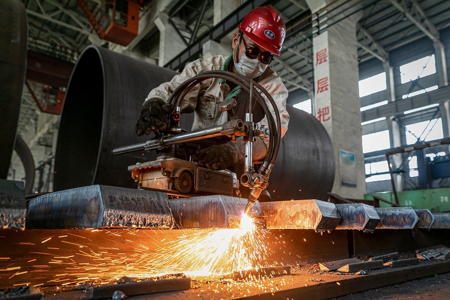 A worker produces a manufacturing machine at a factory in Nantong, Jiangsu province, China, on 26 May 2021. (STR/AFP)