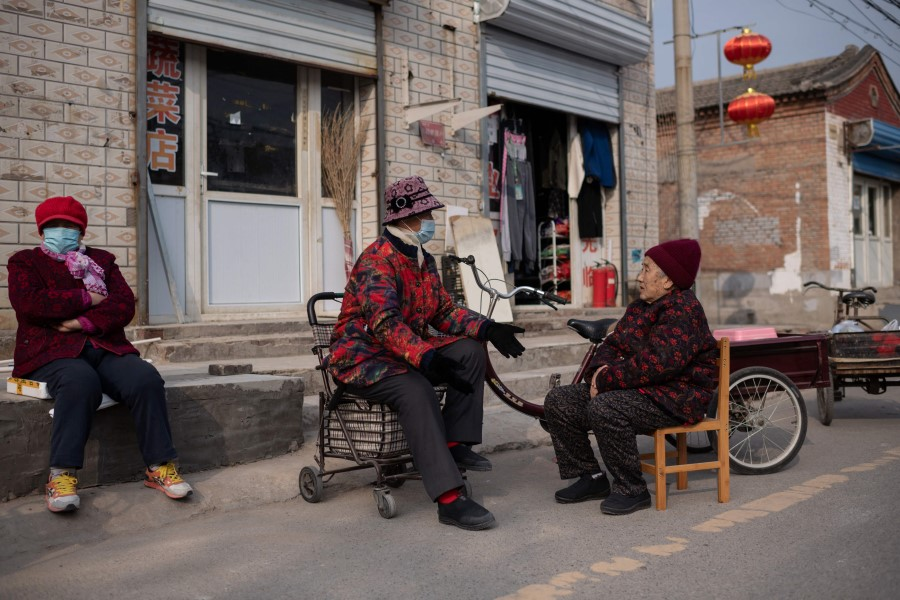 Elderly women chat on a street in Beijing, China, on 6 March 2021. (Nicolas Asfouri/AFP)