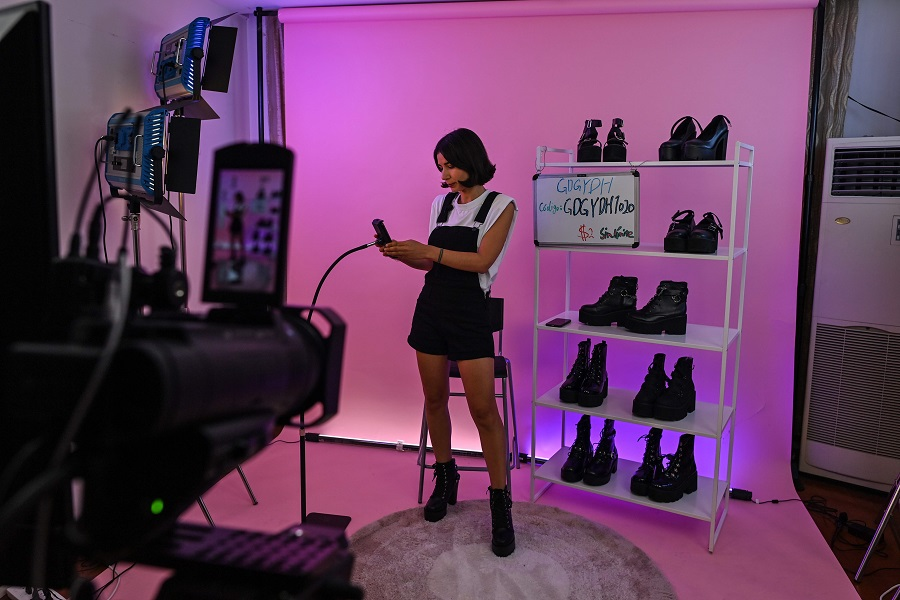 This photo taken early on 23 October 2020 shows an influencer attending a livestreaming event at a studio in Shanghai to offer products on an Aliexpress channel in Spain. (Hector Retamal/AFP)
