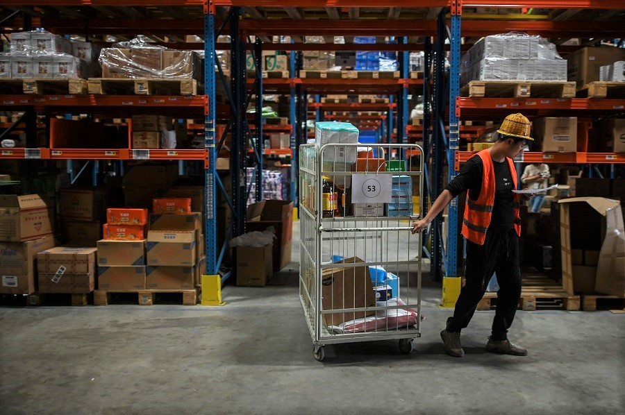 In this picture taken on 6 November 2020, an employee works in the warehouse of Cainiao Smart Logistics Network, the logistics affiliate of e-commerce giant Alibaba, in Wuxi, Jiangsu province, China, ahead of the Singles' Day sales. (Hector Retamal/AFP)