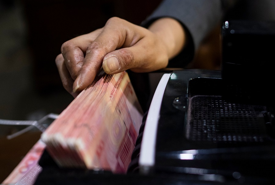 A bank employee uses a money counting machine to count out 100 RMB notes at a bank in Shanghai on 8 August 2018. While China has agreed on a debt suspension initiative, Chinese academics think that China still expects debt to be eventually repaid. (Johannes Eisele/AFP)