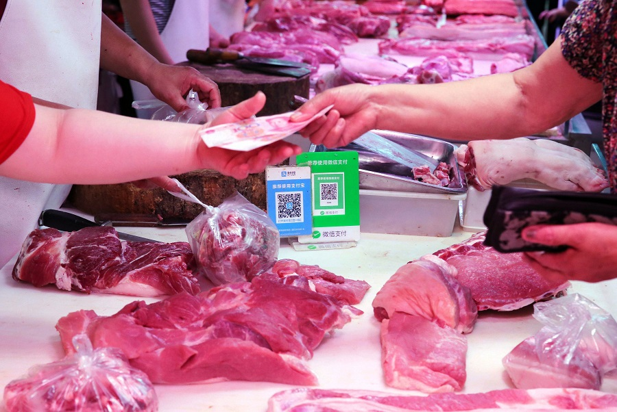 Alipay and wechat QR codes for online payment are displayed as a vendor (left) receives money from a customer at a meat stall in Nantong, Jiangsu, China, on 9 August 2018. (AFP)