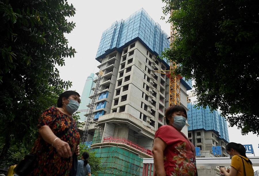 Pedestrians walk in front of an under construction Evergrande housing complex in Shenzhen, China, on 16 September 2021. (Noel Celis/AFP)
