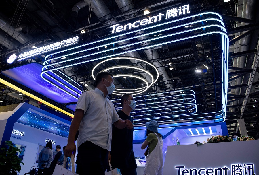 People walk past the Tencent booth at the China International Fair for Trade in Services (CIFTIS) in Beijing on 6 September 2020. (Noel Celis/AFP)