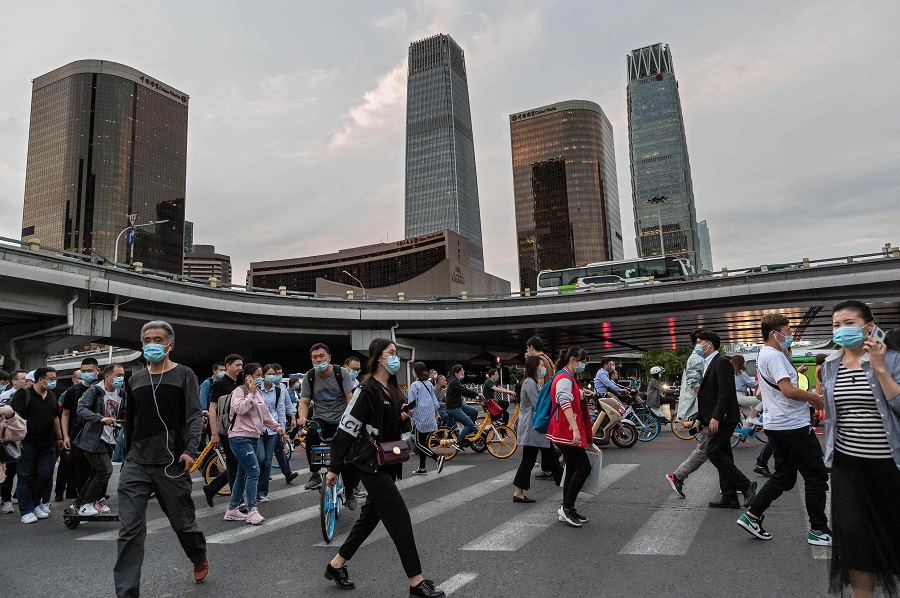 In this picture taken on 22 September 2020, people cross a road during the evening rush hour in Beijing. (Nicolas Asfouri/AFP)
