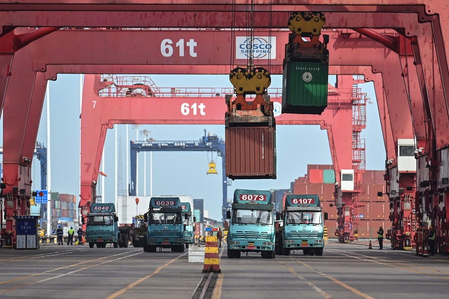 Cranes load containers on trucks at the Lianyungang Port Container Terminal in Lianyungang, Jiangsu province, China, 24 March 2021. (Hector Retamal/AFP)