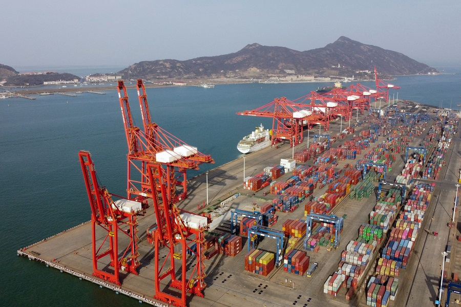 An aerial picture shows container cranes and containers at the Lianyungang Port Container Terminal in Lianyungang, Jiangsu province, China, on 24 March 2021. (Hector Retamal/AFP)