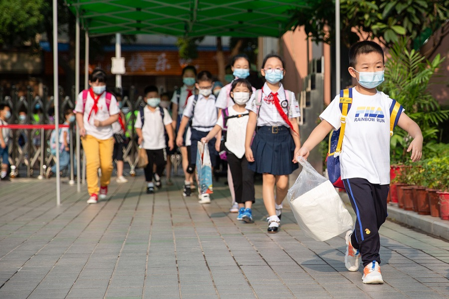 This photo taken on 1 September 2020 shows elementary school students arriving at school on the first day of the new semester in Wuhan, Hubei, China. (STR/AFP)
