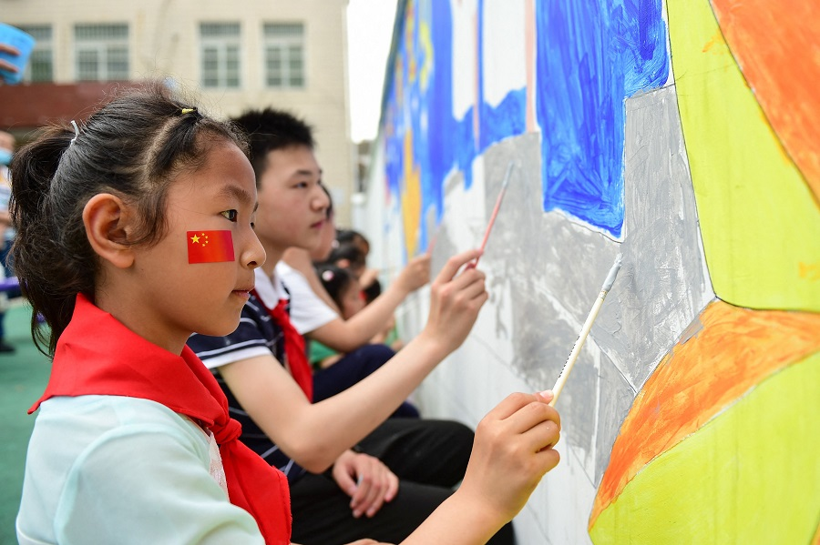 This photo taken on 27 May 2021 shows a student painting on a wall ahead of the Children's Day in Hefei, Anhui province, China. (STR/AFP)