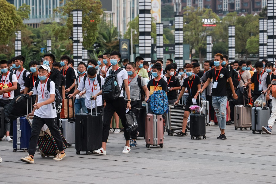 Technical school students arrive at Chongqing North Railway Station as they leave for their internship on the first day of the new semester in Chongqing, China, 1 September 2020. (STR/AFP)