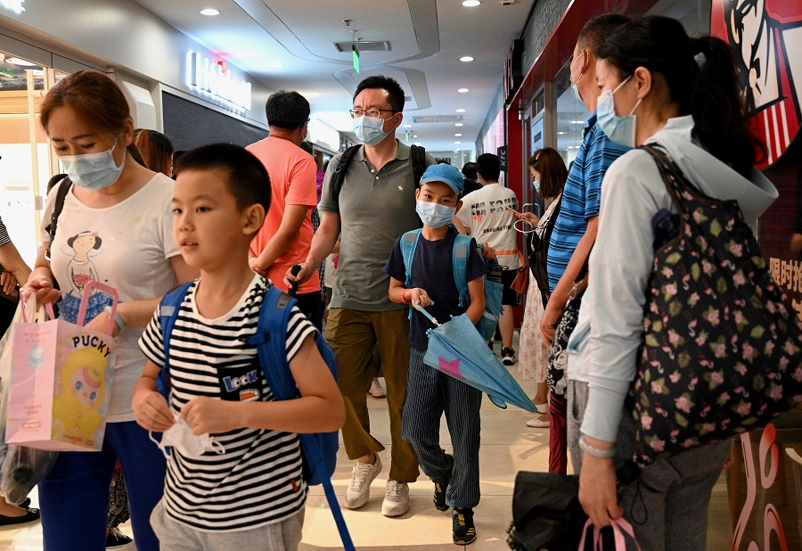 This picture taken on 29 July 2021 shows students and parents walking after attending a private after-school education in Haidan district of Beijing, China. (Noel Celis/AFP)