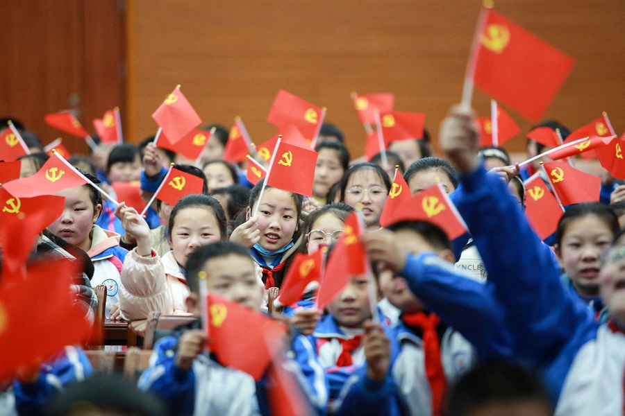 """This photo taken on 23 March 2021 shows students waving flags of the Communist Party as they prepare to watch a movie """"The Founding of a Party"""" in Yangzhou, Jiangsu province, China, to mark the 100th anniversary of the founding of the Communist Party of China. (STR/AFP)"""