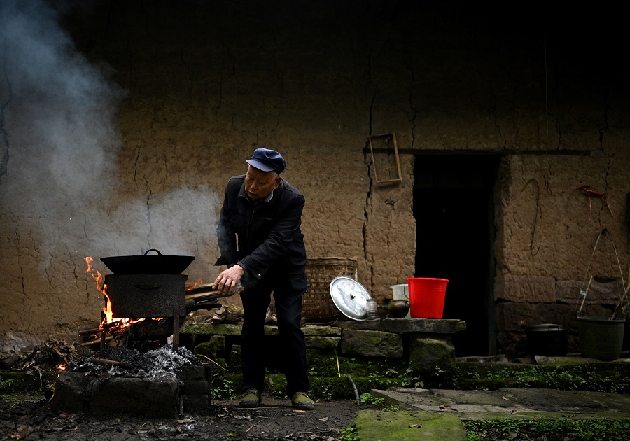 This photo taken on 29 November 2020, shows a man cooking a meal in front of his house in Zhongba, a small island near Chongqing, China. (Noel Celis/AFP)