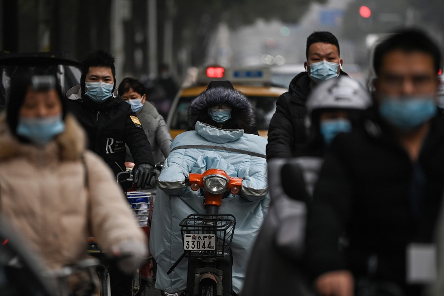Mask-clad commuters ride on a road in Wuhan, Hubei province, China, on 28 January 2021. (Hector Retamal/AFP)