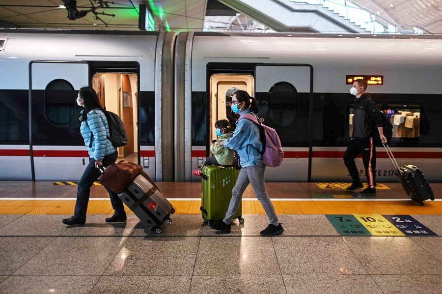 People wearing face masks as a preventive measure against the Covid-19 coronavirus arrive to board a train heading to Shanghai at Wuhan Railway Station in Wuhan, China, on 21 April 2020. (Hector Retamal/AFP)