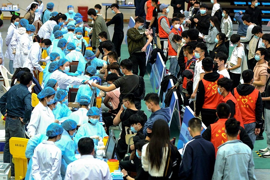 This photo taken on 30 March 2021 shows university students queueing to receive the Sinovac Covid-19 coronavirus vaccine at a university in Qingdao, Shandong province, China. (STR/AFP)