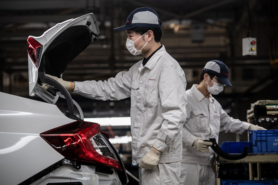 This photo taken on 23 March 2020 shows employees wearing face masks working on an assembly line at an auto plant of Dongfeng Honda in Wuhan, Hubei, China. (STR/AFP)