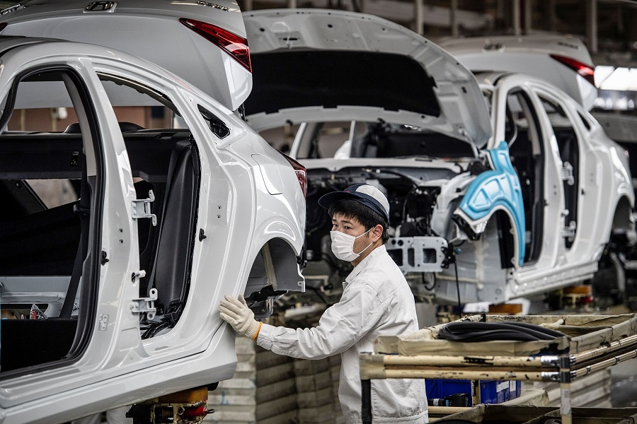 This photo taken on 23 March 2020 shows an employee wearing a face mask working on an assembly line at an auto plant of Dongfeng Honda in Wuhan in China's central Hubei province, as the country slowly gets back to work. (STR/AFP)